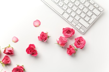 Keyboard with pink roses on white background. Flat lay