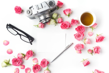 Vintage camera pink roses and note on white background. Top view