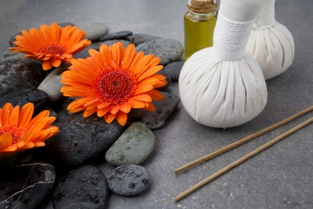 compress: Spa massage setting with rolled towel, thai herbal compress balls and flowers on grey surface