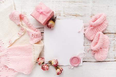 목조 배경에 빈 카드와 함께 아기 소녀 옷. 평평한 평신도. 오워 하드 전망