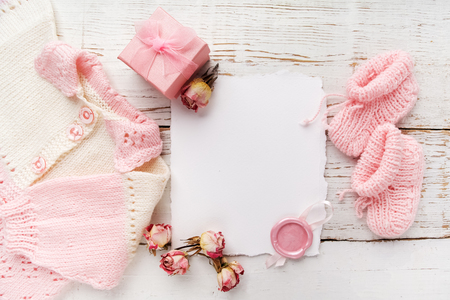 Baby girl clothes with blank card on wooden background. Flat lay. Owerhad view