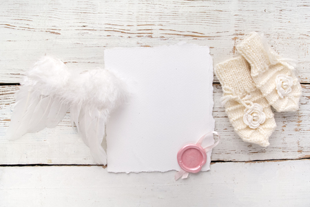 Baby New Born or baptism Greeting Card. Blank card with baby girl gloves and angel wings on white wooden background. Archivio Fotografico