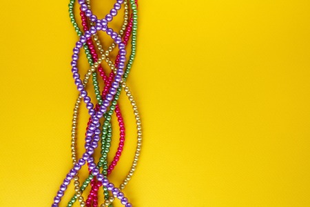 Multi color Mardi Gras beads on paper background. Top view