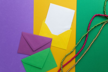 Multi color Mardi Gras beads and envelop with card on paper background. Top view