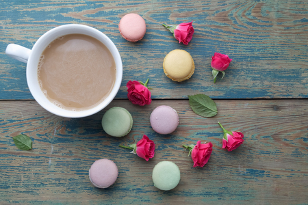 Macaroons, coffee and rose on green wooden background. Top view. Flat lay