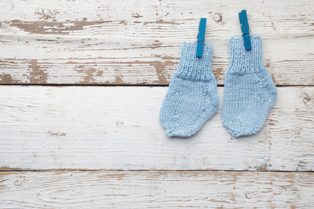 Baby socks hanging on white wooden background. Flat lay