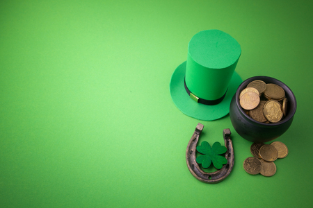 Happy St Patricks Day leprechaun hat with gold coins and lucky charms on green background. Top view.