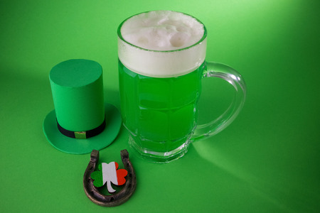 goodluck: St Patricks Day green beer with shamrock, horseshoe and Leprechaun hat against green background.