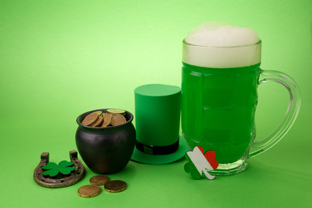 St Patricks Day green beer with shamrock, pot with gold coins, horseshoe and Leprechaun hat against green background.