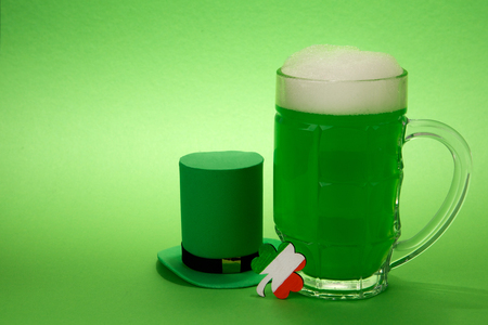 goodluck: St Patricks Day green beer with shamrock and Leprechaun hat against green background. Stock Photo