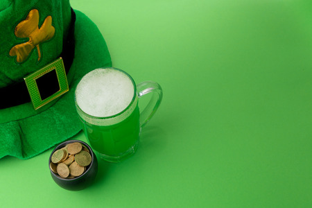 goodluck: St Patricks Day green beer with shamrock, pot with gold coins, horseshoe and Leprechaun hat against green background.