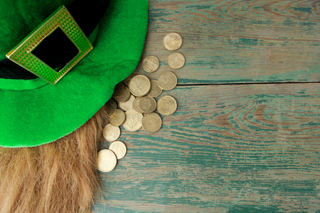 saint paddy's: Happy St Patricks Day leprechaun hat with gold coins on green wood background. Top view Stock Photo