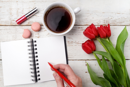 Red tulips, coffee cup and notebook over white wood table. Flat lay Standard-Bild
