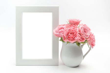 Home decoration, picture frame and cup with roses on white background