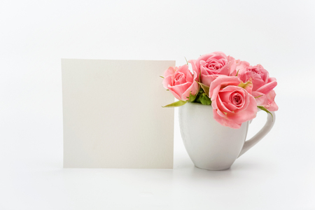 Home decoration, empty card and cup with roses on white background