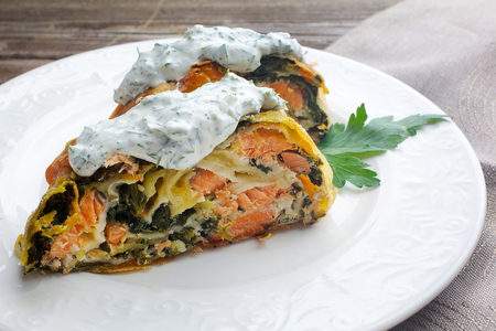 Strudel pie with salmon and spinach, served on wood background Stock Photo