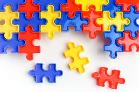 Pieces from a colorful jigsaw puzzle arranged to form a page on white background. Break barriers together for autism concept