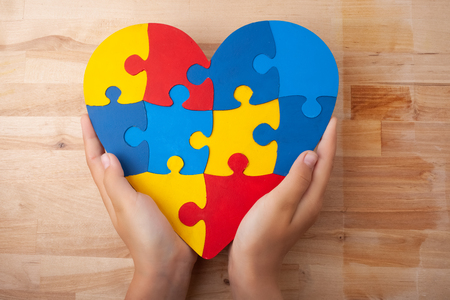 World Autism Awareness day, mental health care concept with puzzle or jigsaw pattern on heart with childs hands