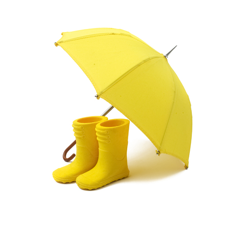 A pair of yellow rain boots and a umbrella on a white