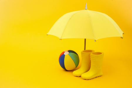 A pair of yellow rain boots and a umbrella and ball on a yellow Stock fotó