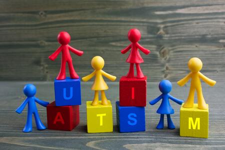 Doll children design with autism word on wooden background