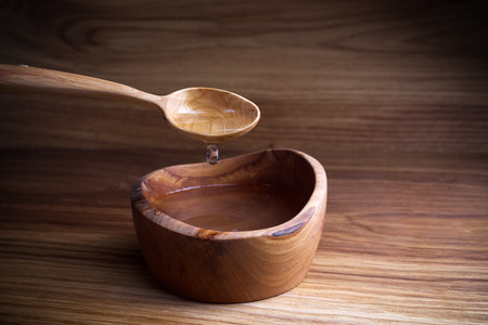 Fasting, Lent. Spoon and cup of water on wooden background