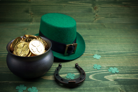 Happy St Patricks Day leprechaun hat with gold coins and lucky charms on vintage style green wood