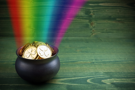 Pot Of Gold on green woden background. Magical Treasure with Rainbow Stok Fotoğraf
