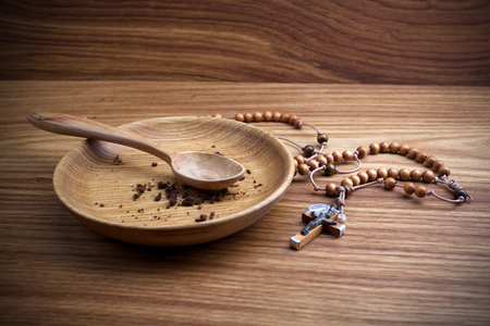 Fasting, Lent. Plate and cross on wooden backgroud.