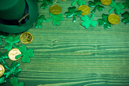 St Patricks Day frame of shamrocks, gold coins and leprechaun hat on green wood