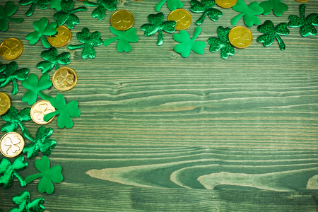 St Patricks Day corner border of shamrocks and gold coins on green wood background