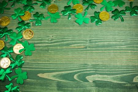 St Patricks Day hoekrand van shamrocks en gouden munten op groene houten achtergrond Stockfoto