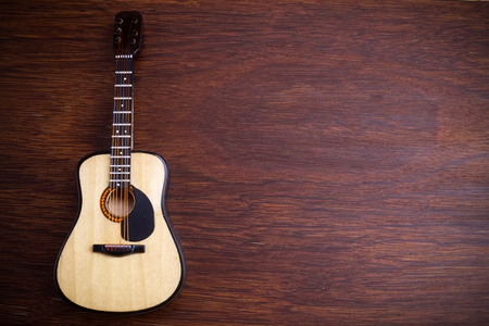 Acoustic guitar against an old wooden background. Фото со стока