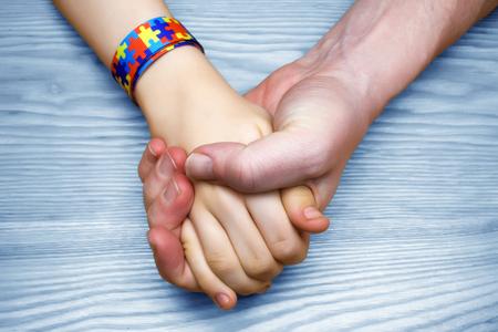Imagen de concienciación sobre el autismo. Padre, tenencia de la mano, ella, niño autista Foto de archivo