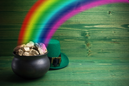 Pot Of Gold on green woden background. Magical Treasure with Rainbow Stockfoto