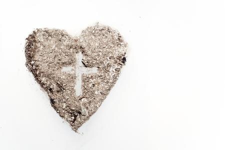 Kreuz oder Kruzifix im Herzsymbol aus Asche, Fastenzeit und Aschermittwoch-Konzept