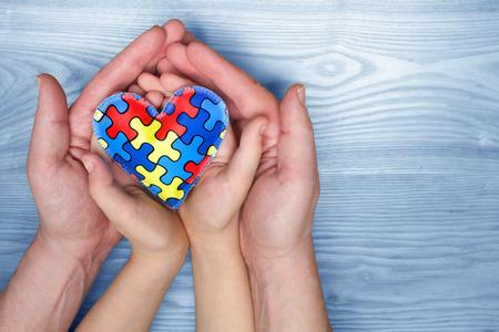 Día mundial de concientización sobre el autismo, rompecabezas o patrón de rompecabezas en el corazón con niños autistas y manos del padre Foto de archivo