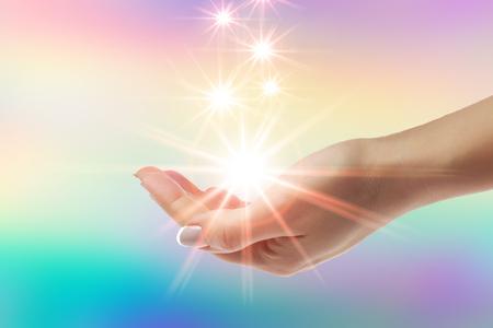 Guérir les mains avec un rayon de soleil brillant sur fond arc-en-ciel Banque d'images