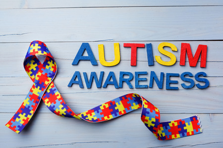 World Autism awareness and pride day or month with Puzzle pattern ribbon on blue wooden background. 版權商用圖片