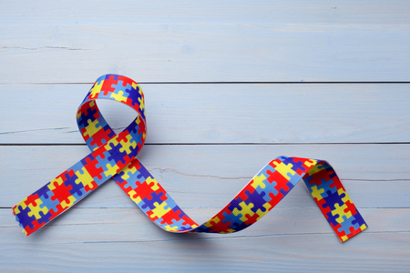 World Autism awareness and pride day or month with Puzzle pattern ribbon on blue wooden background. Stock Photo