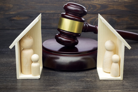 Gavel showing separation of family and house on dark wooden background