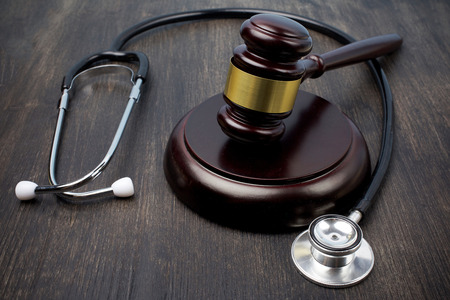 Gavel and stethoscope on black wooden background