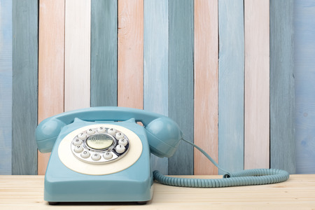 Retro background with vintage telephone on wood table