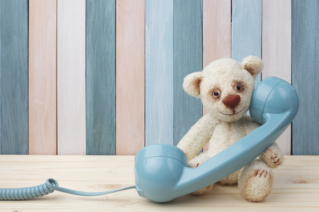 Vintage teddybeer met retro telefoon op houten achtergrond