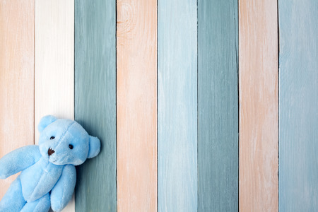 Teddy Bear toy alone on pastel wooden background