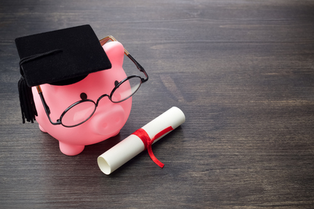 Piggy bank with a grad cap and diploma on wooden table, Education scholarship