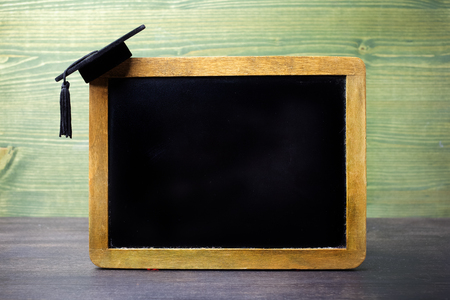 black chalkboard with a graduation cap hanging on the corner