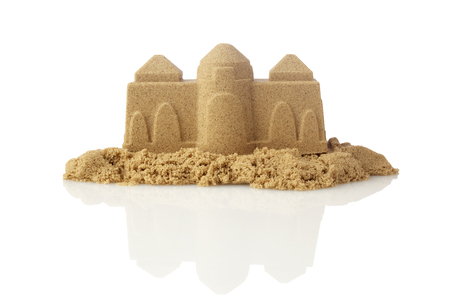 Sandcastle at the beach isolated on white background