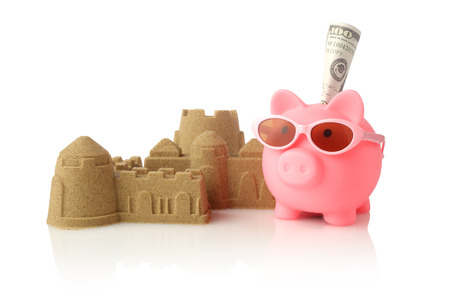 Piggy bank wearing retro sunglasses and sandcastle isolated on white background