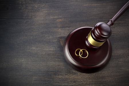 Wedding rings hammer of a judge on a dark wooden background. Divorce proceedings